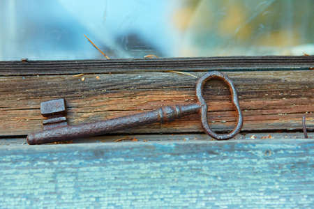 An old beautiful rusty key is lying on the window of an old house