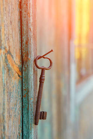 A vintage rusty key hangs on a nail on the wall of an old house, at dawn 版權商用圖片