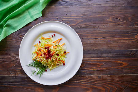 Fresh cabbage salad made from shredded white cabbage, carrots and berries on a white plate. Top view, wooden background, selective focus