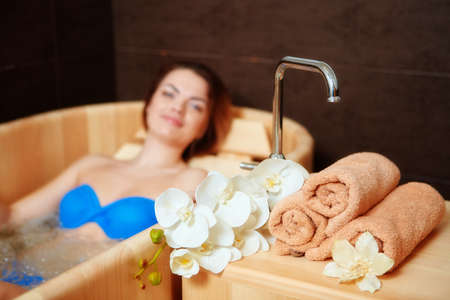 A woman who has Spa treatment and recreation in a wooden hot tub made of cedar