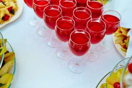 A row of glasses with red drinks, juice, champagne or wine at a party. Catering. Glassware on the table with a white tablecloth. Festive buffet for the holiday.