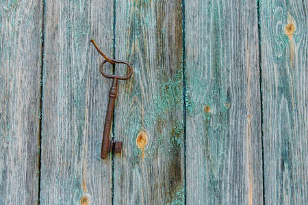 An old forged beautiful rusty key hangs on an old iron nail on a wooden wall, with peeling paint 版權商用圖片