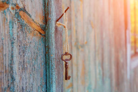 A vintage rusty key hangs on a nail on the wall of an old house, at dawn.