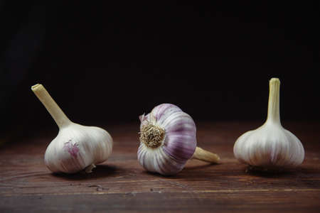 Three ripe heads of fresh garlic on a dark wooden background. Folk medicine for viral and colds