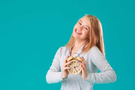 Cute laughing positive girl in sports clothes holding an alarm clock. Turquoise background 版權商用圖片