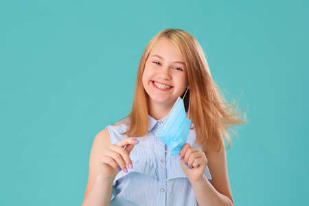 Portrait of a laughing young girl with a medical mask in her hands on a blue background. She is happy that the coronavirus has been defeated and everyone is healthy