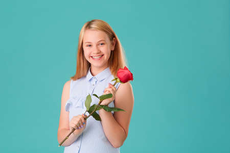 A happy girl holds a red rose in her hands. Romantic gift.