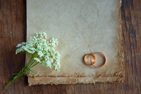 Wedding rings and a wild flower are on antique paper. Symbols of eternal love. Recognition on Valentines day with a place for your text 版權商用圖片