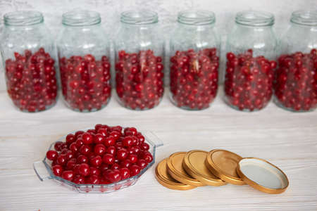 Preserving cherries in glass jars for the winter or in case of self-isolation in quarantine. Homemade fruit stocks in their own juice. Cherry compote with your own hands. 版權商用圖片