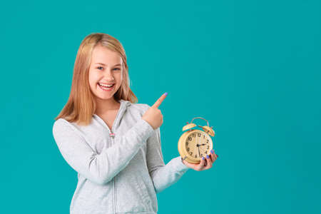 A teenage girl holds an alarm clock, standing on an isolated turquoise background, happy and laughing. Makes a hand gesture to an empty space for your text