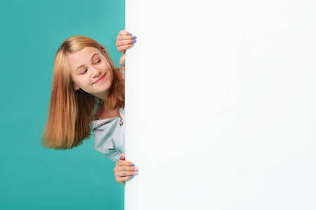 A smiling girl stands behind a white blank panel isolated against a turquoise background. Looks out from behind the banner, an empty space for the text ..