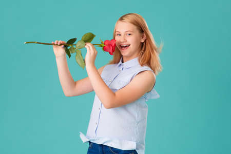 The girl laughs, and sniffs a red rose, in the Studio on a turquoise background