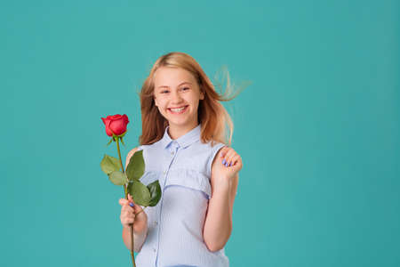 A happy laughing girl holds a red rose on a turquoise background
