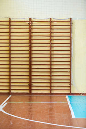 Gym for sports classes at school or College. Swedish wall, stairs, and wooden floor with markings for volleyball 免版税图像