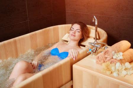 Young woman relaxing in wooden bath. 免版税图像