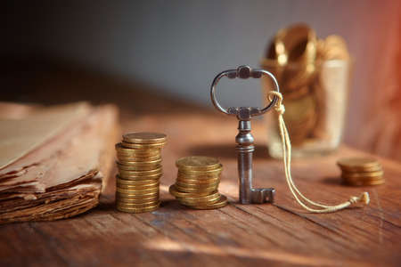 An old beautiful old key, a stack of gold coins, an old parchment. Business start-up, investment, treasure hunting, or the concept of the key to success