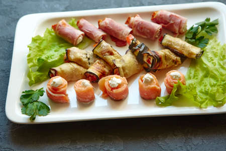 A dish with mini-canapes of salmon, eggplant and ham rolls with different fillings for a buffet and a festive table.
