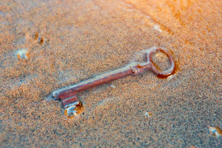 The sea washed up on the sandy beach an old vintage key to a treasure chest. The concept of success, luck and wealth.