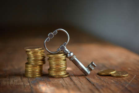An old beautiful antique key and a stack of gold coins. Business start-up, investment, treasure hunting, or the concept of the key to success 免版税图像