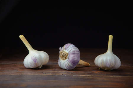Three ripe heads of fresh garlic on a dark wooden background. Folk medicine for viral and colds.