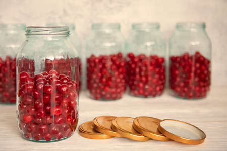 Not closed glass jars with cherries, prepared for canning with tin screw lids. 免版税图像