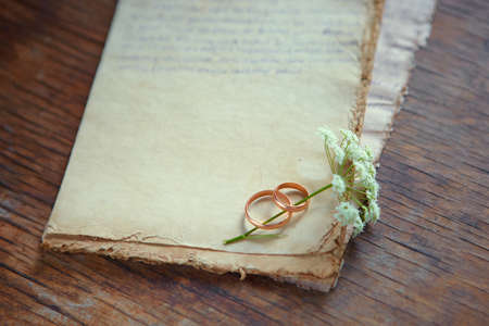 Wedding rings and a wild flower are on antique paper. Symbols of eternal love. Recognition on Valentine's day with a place for your text.
