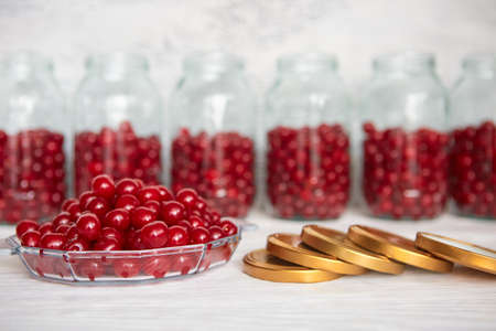 Preserving cherries in glass jars for the winter or in case of self-isolation in quarantine. Homemade fruit stocks in their own juice. Cherry compote with your own hands 免版税图像