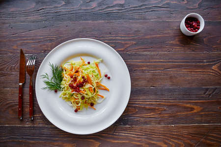 Fresh cabbage salad made from shredded white cabbage, carrots and berries on a white plate. Top view, wooden background, selective focus.