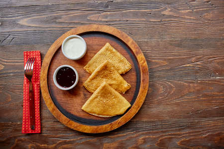 Homemade hot delicious pancakes with sour cream and jam on a wooden plate, top view 免版税图像