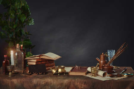 Old books, scrolls, pen and inkwell, antique objects made of gold and brass on a dark background. Space for your text