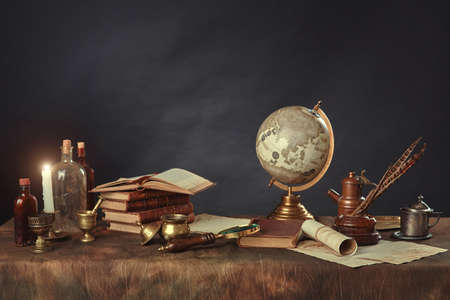 Desktop of a scientist, writer, or student of past centuries. Vintage items, books and manuscripts on a dark background. Space for your text