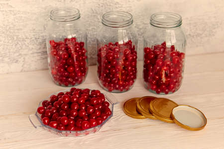 Production of cherry compote in jars. Homemade canned food. The concept of handmade.