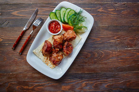 Shashlik, meat cooked on skewers on an open table, in a white plate on a wooden background.