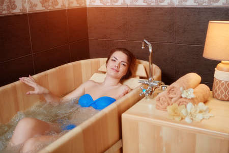 A young beautiful girl relaxes in a wooden hot tub made of wood.