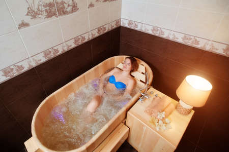 A young girl enjoys an eco-friendly wooden Jacuzzi bath.