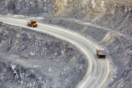 Top view of working BelAZ dump trucks in a stone and crushed stone quarry in Russia, Chelyabinsk region, Miass city. 免版税图像