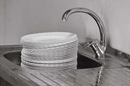 A big pile of dishes in the sink under the water tap.