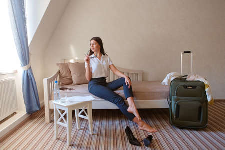 A beautiful dark-haired woman is sitting on a sofa in a hotel room. She took off her shoes after a day of work and continues to work, staying in touch with the office. Stock fotó