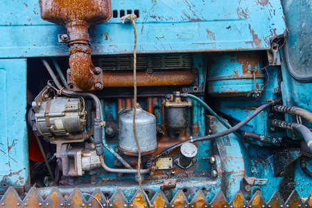 View of an old oiled and rusted tractor engine, background.
