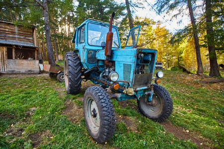 An old blue tractor stands in a farmyard.