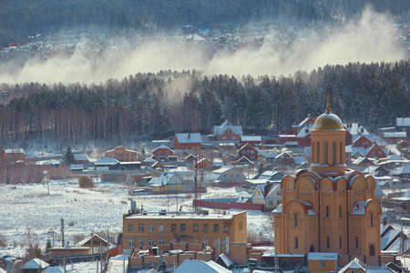 Winter rural landscape with a snowstorm in the Russian Urals with snow covered wooden houses