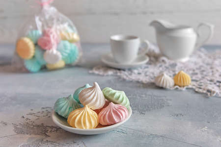 Romantic Breakfast with meringue cookies, white cups and creamer.