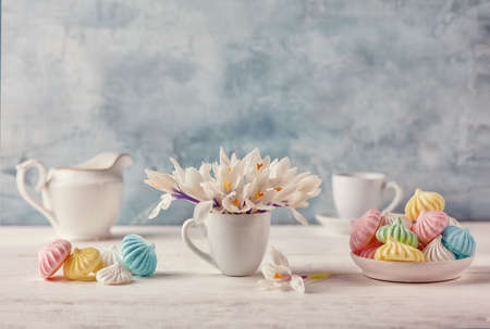 Romantic Breakfast with a Cup of tea, Crocus flowers and sweet multi-colored meringue on the wooden table 免版税图像