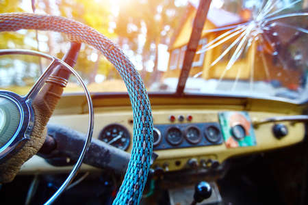 Vintage interior of an old car with a retro dashboard and steering wheel in a PVC cover. 免版税图像