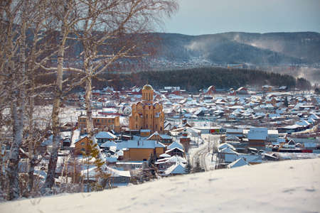 Russian village winter. Roofs covered with snow, a Blizzard sweeps in the forest.