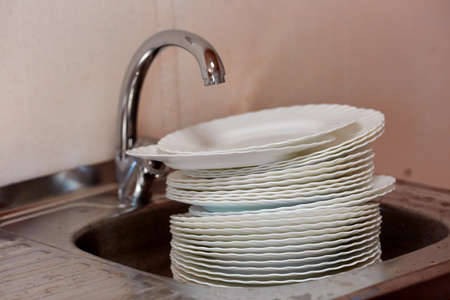 A pile of dirty dishes stands under a running water tap in a steel sink.