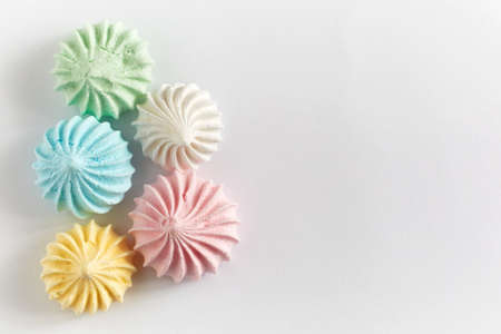Pastel colored meringue on white background.