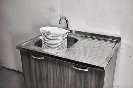 A large stack of dirty China plates is in the metal sink under the water tap in the dirty kitchen.