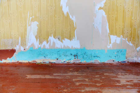 A fragment of a living room with an old wooden floor with peeling paint and a wall with torn Wallpaper covered with rot and mold. The concept of poverty.