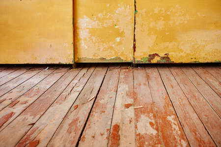 A fragment of a living room with an old wooden floor with peeling paint and a dilapidated wardrobe.